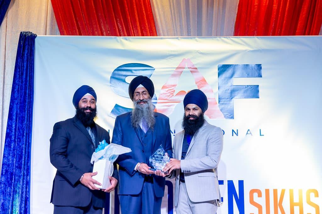 Dr Suneet Singh Tulli handed over an appreciation award by Manveer and Shamandeep Singh of SAF International.